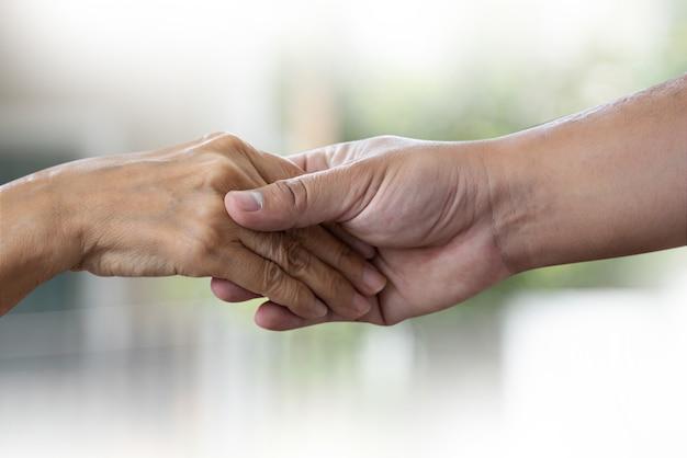 Alte frau und junge hand der leute, die das behinderte gehen mit unterstützung hält