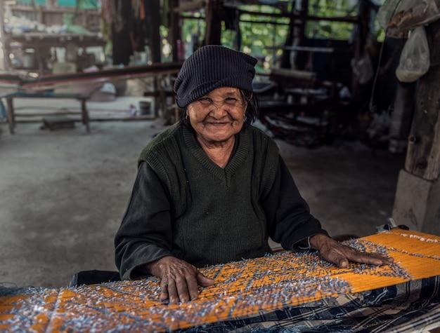 Alte frauen demonstrieren dem verfahren zur herstellung von thai-seidenweben