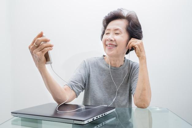 Alte frauen, die musik vom mobile hören