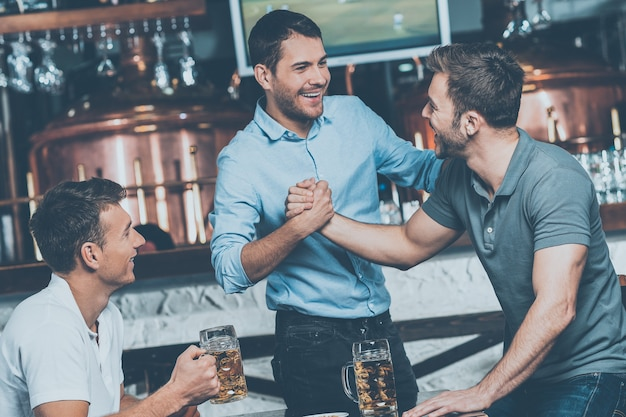 Alte freunde treffen. drei fröhliche freunde treffen sich in einer bierkneipe