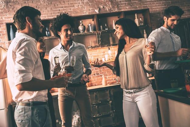 Alte freunde treffen. gruppe fröhlicher junger leute, die eine heimparty mit snacks und getränken genießen, während sie in der küche kommunizieren communicating