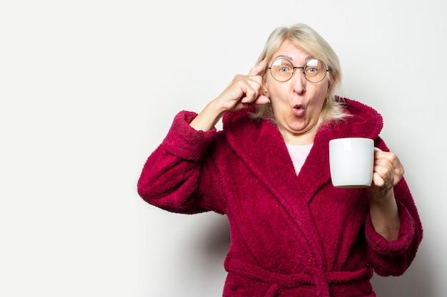 Alte freundliche frau mit einem überraschten gesicht in einem alltäglichen schlafrock und einer brille hält eine tasse und zeigt mit seiner zweiten hand mit dem finger auf den tempel an der hellen wand. morgenkaffee-konzept, denken sie