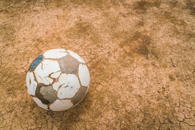 Alte fußballkugel auf trockenen und rissigen boden textur.
