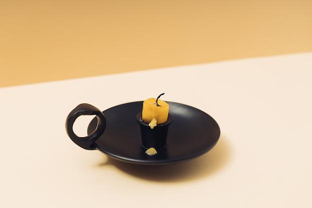 Alte gebrannte wachskerze in einem schwarzen vintage-kerzenhalter auf einem geometrischen gelben hintergrund.