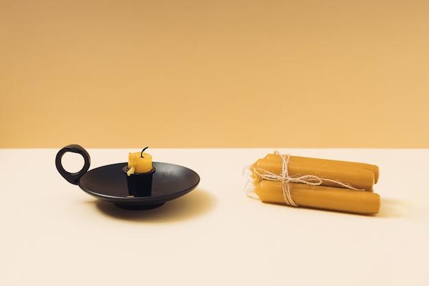 Alte gebrannte wachskerze in einem schwarzen vintage-kerzenhalter und ein stapel neuer kerzen auf einem geometrischen gelben hintergrund.