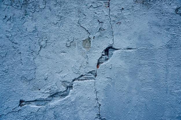 Alte gebrochene blaue wand auf dem straßentexturhintergrund