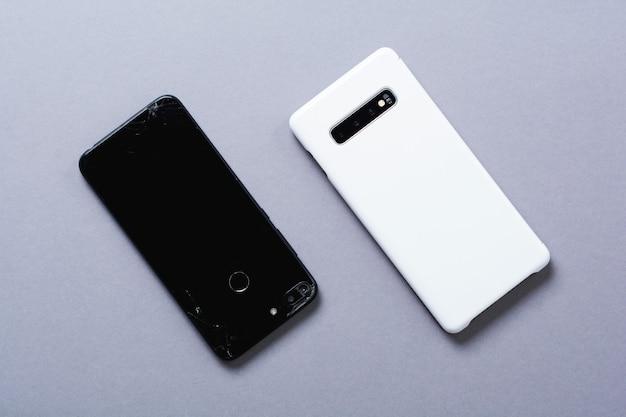 Alte gebrochene schwarze und neue weiße smartphones auf grauem hintergrund. das konzept des recyclings von telefonen und technologien. draufsicht.