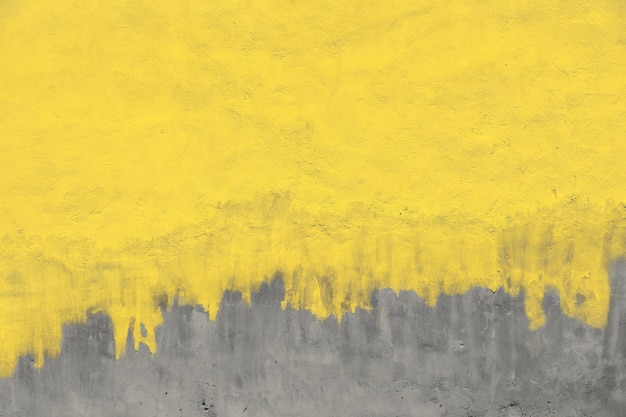 Alte gelb gestrichene graue putzbetonwand mit wetterflecken, läufen und mängeln