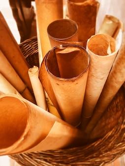 Alte gerollte schriftrollen in einem geflochtenen korb