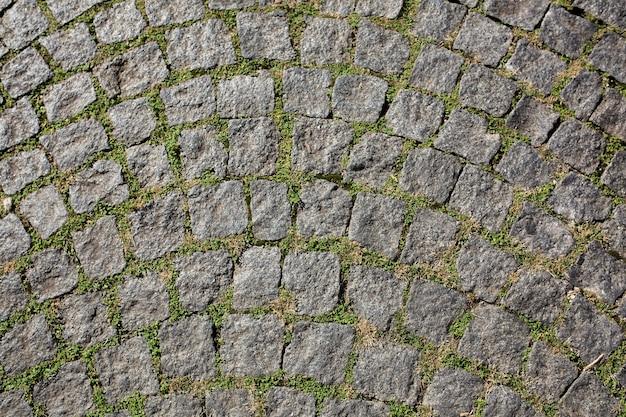 Alte gerundete pflastersteine mit gras in prag