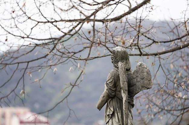 Alte grabsteinskulptur eines engels mit gebrochenem arm und flügeln auf dem friedhof