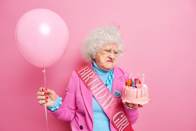 Alte grauhaarige schöne frau sieht unzufrieden auf geburtstagskuchen traurig über das älterwerden trägt eine brille festliches outfit hält aufgeblasenen ballon nimmt glückwünsche entgegen
