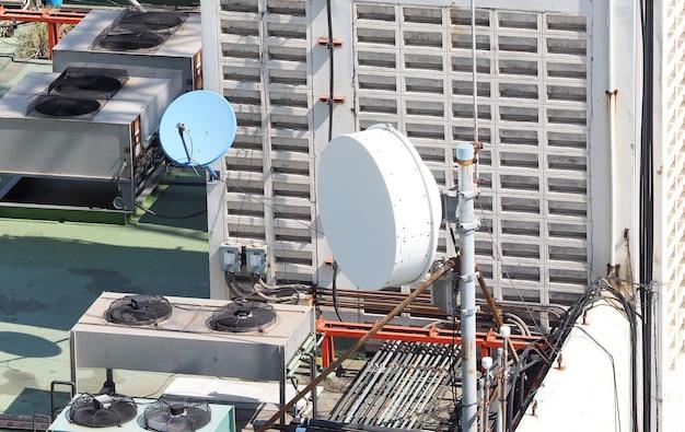 Alte große telekommunikations-satellitenschüssel auf dem dach des gebäudes.