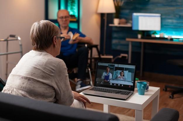 Alte großmutter, die den arzt in der klinik auf der krankenstation anruft, um die gesundheitsdiagnose auf der videokonferenz zu überprüfen. frau, die mit einem arzt über die behandlung einer nichte spricht, während der mann im rollstuhl sitzt