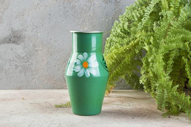 Alte grüne metallvase mit pflanzen auf einer betonoberfläche