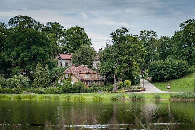 Alte häuser am seeufer mit reflexion im bewölkten sommertag. talsi, lettland.