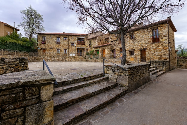 Alte häuser auf einem platz in einer stadt in der sierra de madrid. horcajuelo. madrid. europa.