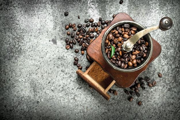 Alte handmühle mit kaffeebohnen. auf einem rustikalen hintergrund.