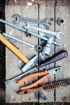 Alte handwerkzeuge verstreut auf der holzoberfläche, draufsicht.