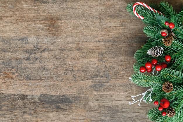 Alte hölzerne beschaffenheit verzieren mit kiefernblatt, kiefernkegeln, stechpalmenbällen und zuckerstange im weihnachtsmotivkonzept