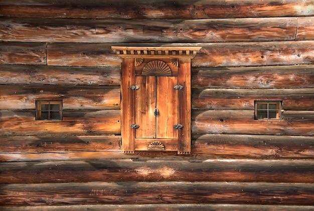 Alte hölzerne fensterläden an einer blockwand. geschnitztes holzfenster. traditionelle russische holzschnitzerei