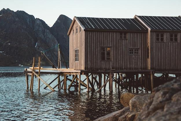 Alte hölzerne fischerhäuser in der nähe des sees vor dem hintergrund der berge. norwegen, europa. platz kopieren. kann als banner verwendet werden.