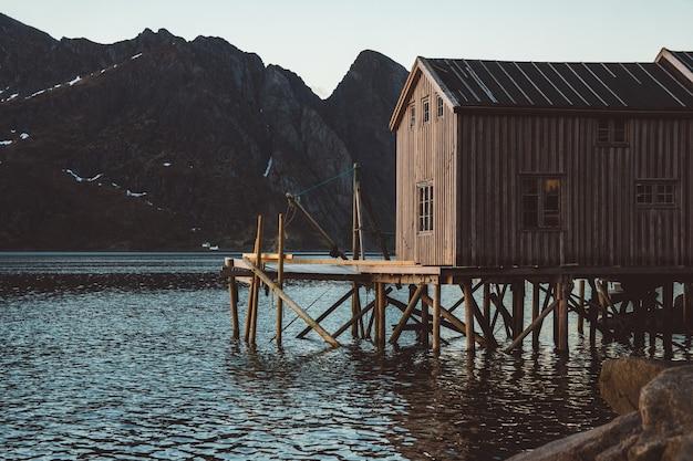 Alte hölzerne fischerhäuser in der nähe des sees vor dem hintergrund der berge