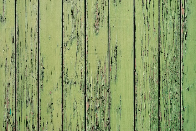 Alte hölzerne gemalte rustikale wand mit grüner flockiger färbung.