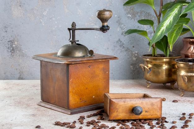 Alte hölzerne kaffeemühle auf konkretem hintergrund.