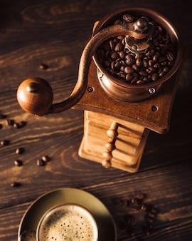 Alte hölzerne kaffeemühle mit bohnen