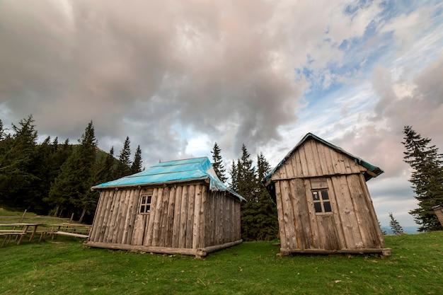 Alte hölzerne schäferhütten auf gebirgsgrünem tal auf blauem kopienraum des bewölkten himmels.