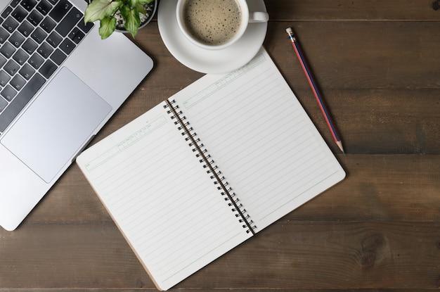 Alte hölzerne schreibtischtabelle mit leerem notizbuch, laptop-computer