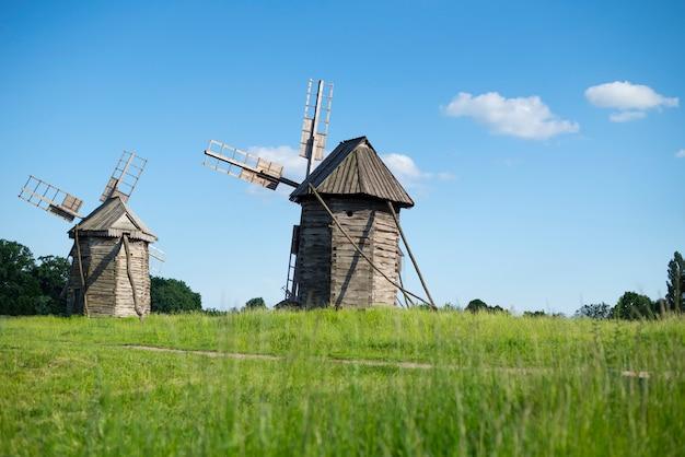 Alte hölzerne windmühlen auf hintergrund des blauen himmels
