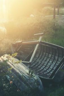 Alte holzboote am seeufer bei sonnenuntergang