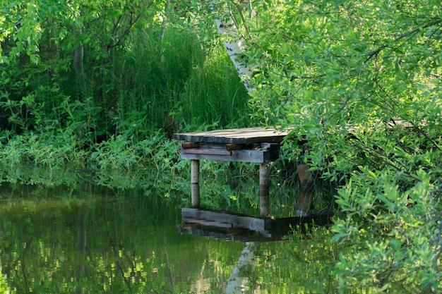 Alte holzbrücke über dem teich.
