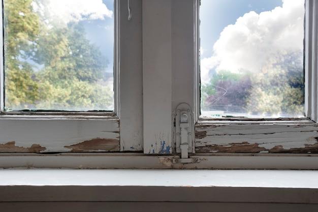 Alte holzfensterrahmen mit verrottendem holz und rissiger peelingfarbe, haus muss renoviert werden und neue rahmen in nahaufnahme
