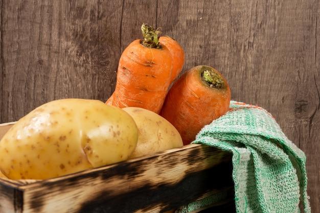 Alte holzkiste füllte frische kartoffeln und karotten