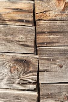 Alte holzoberfläche fotografierte nahaufnahme. schärfe ist nicht die ganze ebene, eine kleine schärfentiefe. holz ist witterungseinflüssen ausgesetzt und weist eine reihe von mängeln auf