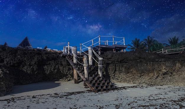 Alte holztreppe, die zum hotel auf hintergrund des sternenhimmels nachtlandschaft afrika, tansania, sansibar führt