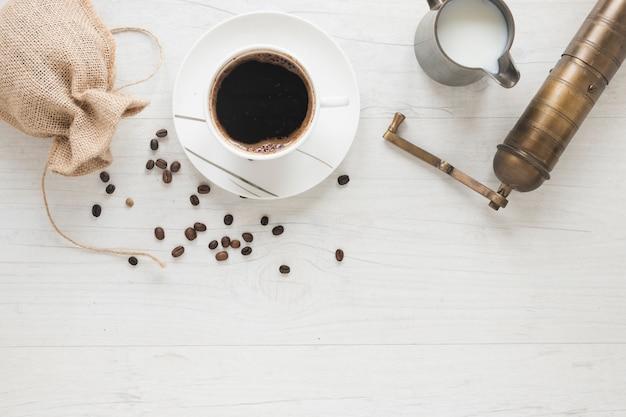 Alte kaffeemühle; kaffeebohnen, die vom sack mit kaffeetasse und milch auf weißem schreibtisch fallen