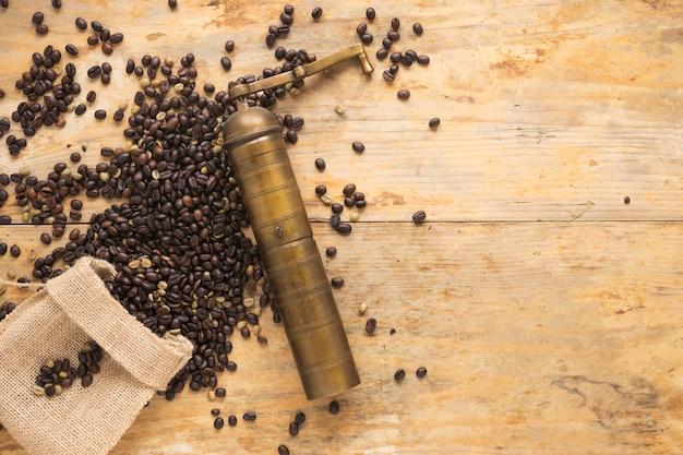 Alte kaffeemühle mit den kaffeebohnen, die vom sack auf tabelle fallen