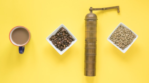 Alte kaffeemühle; rohe und geröstete kaffeebohnen und kaffeetasse über hellgelbem hintergrund