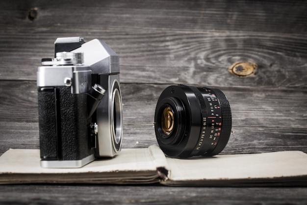 Alte kamera am weinlesebuch, hölzerner hintergrund