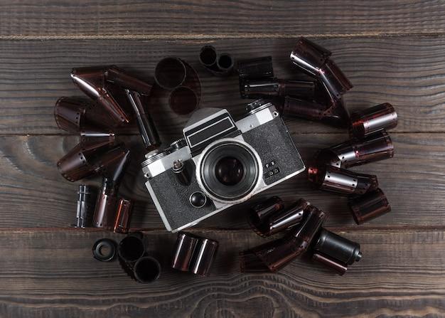 Alte kamera und filme sind auf der dunklen holzoberfläche im retro-stil