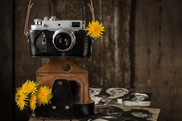 Alte kamera und gelber löwenzahn, weinlesestillleben