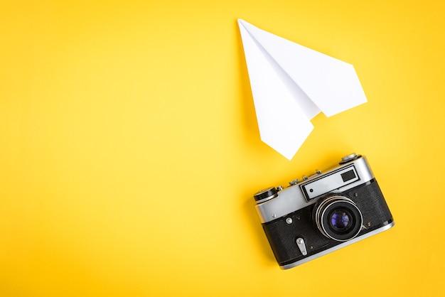 Alte kamera und papierflugzeug auf gelb
