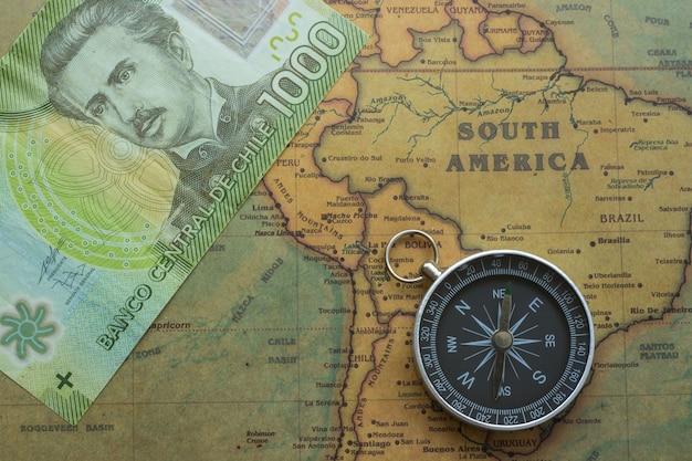 Alte karte von südamerika mit chilenischem geld und kompass,