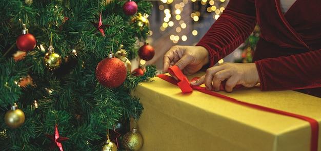 Alte kaukasierin auf pullover, die geschenkbox einwickeln, mit einem band binden und oben zu einer schönen schleife falten, um ein überraschtes wintergeschenk für die neujahrsparty in der nähe des mit ornamenten verzierten weihnachtsbaums vorzubereiten