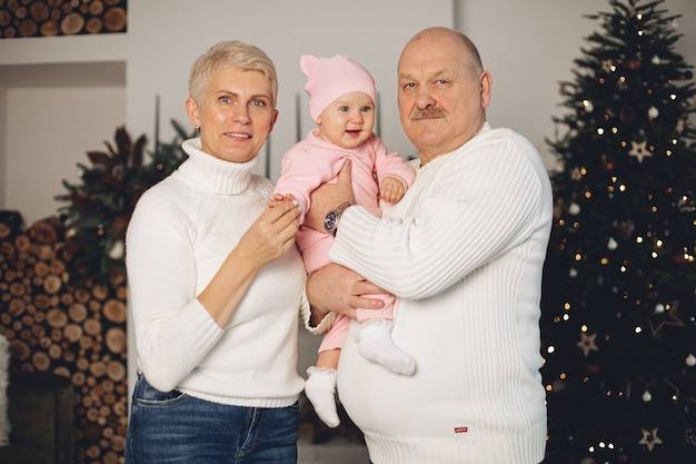 Alte kaukasische frau feiert weihnachten mit ihrem ehemann und ihrer kleinen enkelin