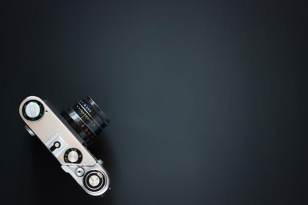 Alte klassische vintage vintage-kamera, die auf der schwarzen oberfläche liegt